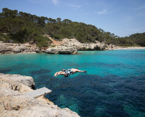mountain biking Menorca diving into Mediterranean Sea