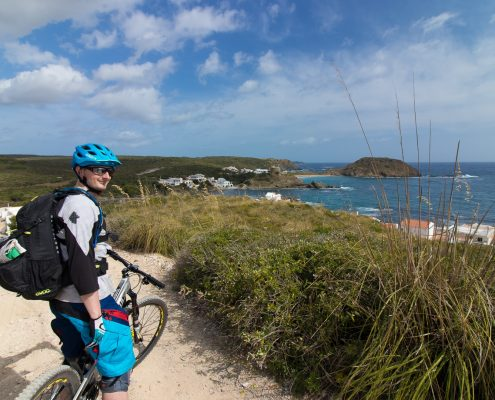 mountain biking Menorca Dustin in front of sea coast panorama